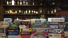Image of stacks and stacks of board games on the bar of Mr. Henry's Upstairs